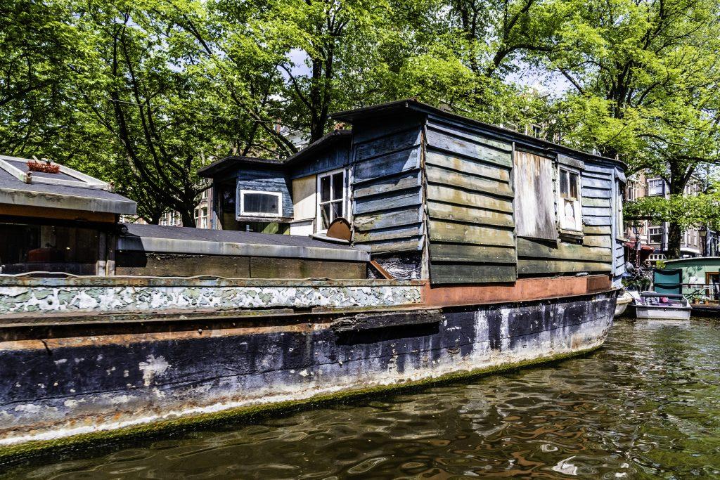 case galleggianti ricavate in ex battelli dismessi ormeggiate lungo i canali di Amsterdam