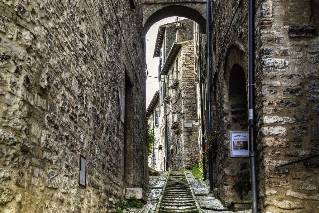 gli stretti vicoli di Spello tra muri di mattoni, e archi in pietra