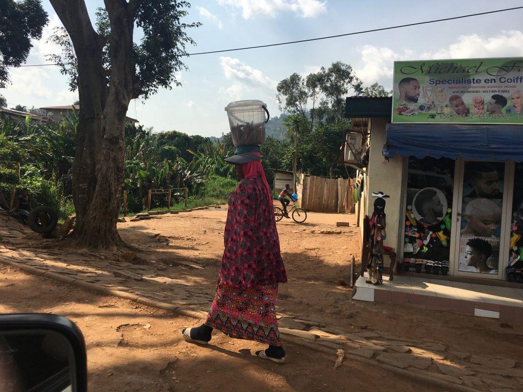 una donna per le strade sterrate di Yaoundé in Cameroun